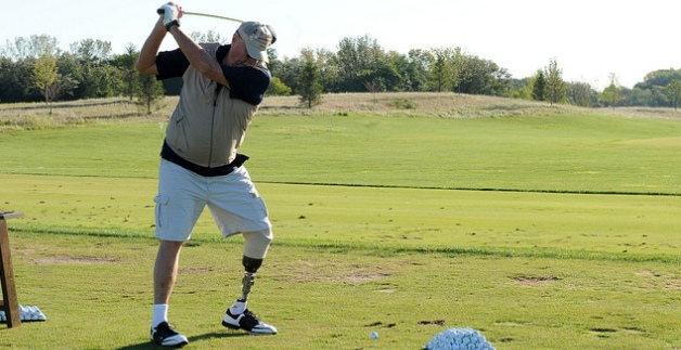 A disabled Veteran takes a swing at a golf ball on a golf course