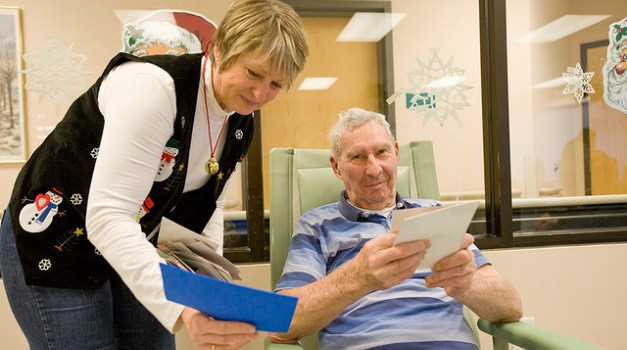 Volunteer at VA hospital, a woman helping a man in a chair