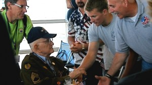 Picture of men shaking the hand of a Veteran in a Wheel chair