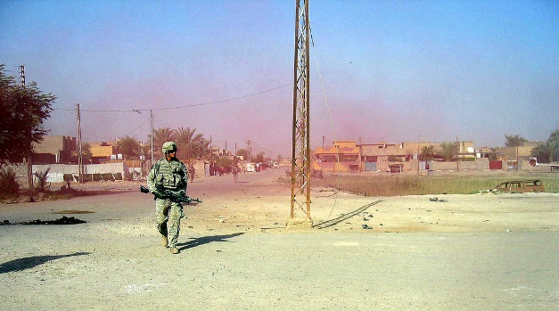 Image of a solider walking through colored smoke