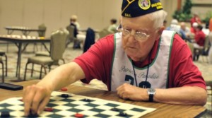 Male Veteran playing checkers at a wooden table.