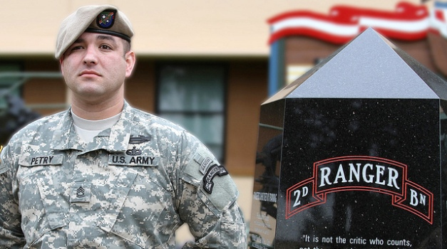 Male soldier standing at parade rest in front of building.