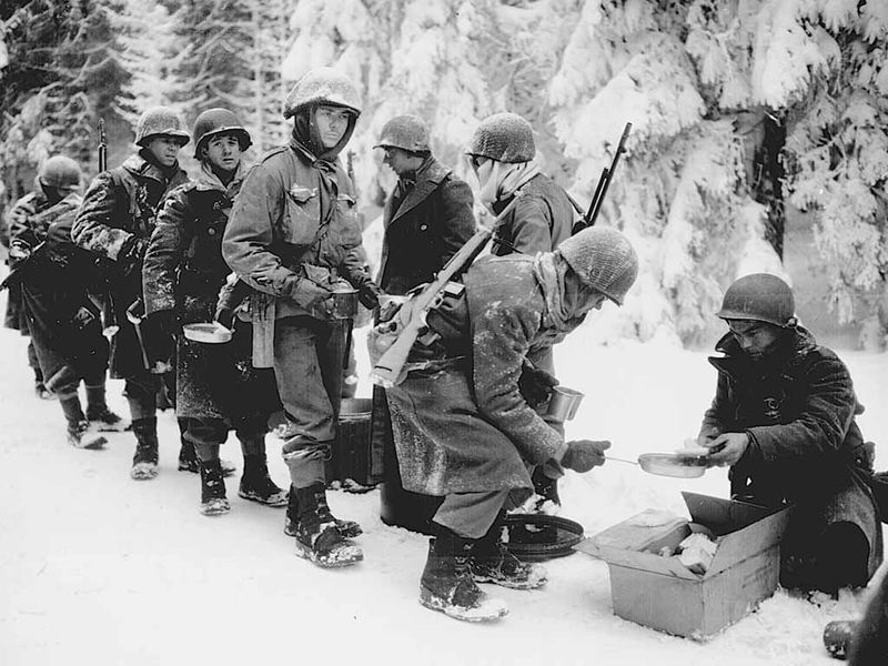 Soldiers with the U.S. Army's 347th Infantry Regiment line wait for a meal on their way to La Roche, Belgium, during the Battle of the Bulge in January 1945. — Courtesy of the National Archives photo no. 111-SC-198849
