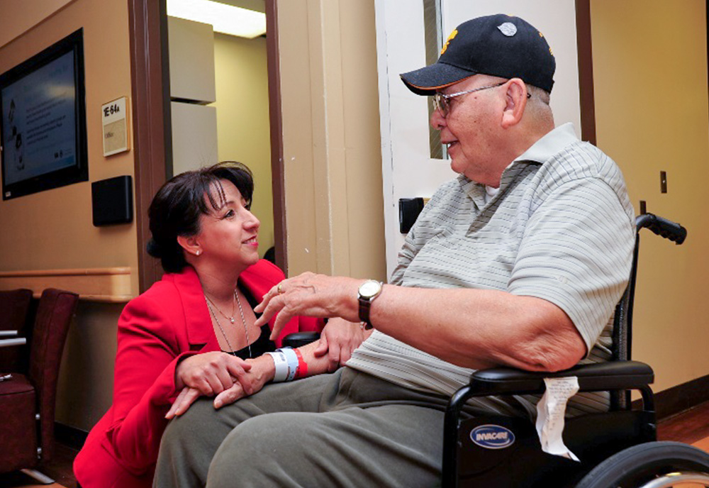 Nurse talking with patient in a wheelchair