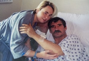 Elise Brown standing next to Roy Jeffers who is laying in a hospital bed