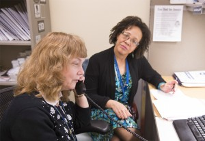 Two women working in an office setting. One woman is talking on the phone.