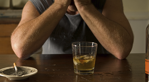 A man at a table covering his face with a cigarette and scotch in front of him.