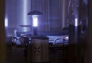 A tall, cylindrical machine stands in the center of a hospital room and emits blue light