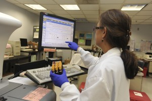 A woman in a lab coat holds viles while touching a computer screen.