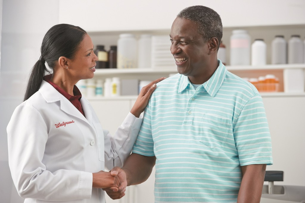 A pharmacist shakes hands with a man.