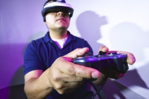 A man wearing a VR visor holds a gaming controller.