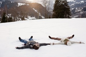 Couple making snow angels
