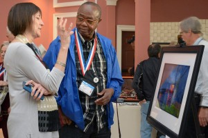 A Veteran discusses his artwork on display at the National Veterans Creative Arts Festival.