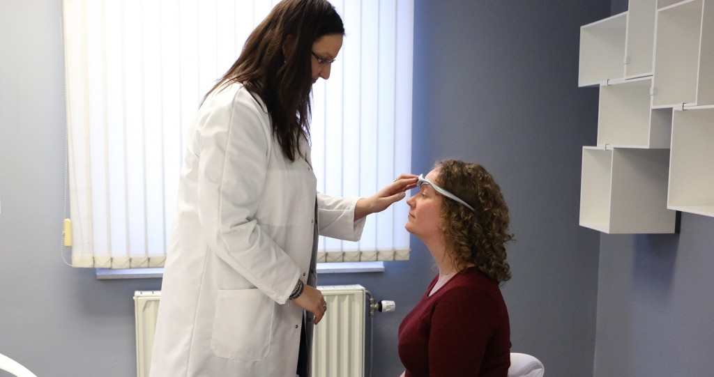 A female doctor places the migraine device on a female patient