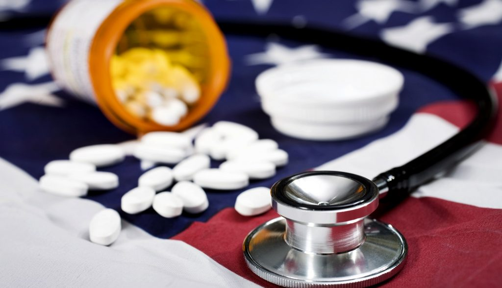 Pills and a stehoscope on an American Flag