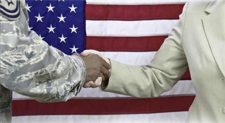 Image of military and civilian shaking hands in front of Old Glory.