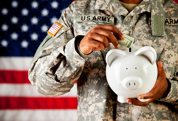 Image of army person in uniform placing money into a piggy bank.
