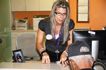 """Image: Angela Warner, Medical Support Assistant, who designed the """"No More Red Tape – Eye and Hearing Exam"""" buttons."""