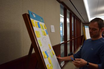 Image of a man infront of a posterboard with a bunch of post-it notes attached.
