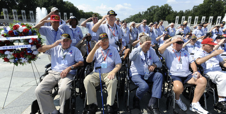 """File Photo: Honor Flights to Washington, D.C.'s war memorials increased significantly after Labor Day, as D.C.'s fabled heat (theoretically) transitions to a more favorable fall climate. Groups from Arizona, Florida, Idaho and Chicago were some of the first to arrive in the nation's capitol Sept. 7 after the federal holiday. Honor Flight Chicago celebrated its 74th flight since its inception, with 108 participants including 18 World War II and 90 Korean War Vets, in addition to the required support staff of more than 125 dedicated volunteers. Their day began much earlier than the 6:45 a.m. flight from Midway Airport-Chicago, to Dulles, Va. They boarded buses and drove to the Iwo Jima Memorial where they were met by police motorcycle escort which guided them first to the Air Force Memorial for a performance by the Air Force Drill Team, before crossing the Potomac to the National World War II Memorial. The group toured the memorial until a color guard honored the Veterans with pomp and circumstance. Center of the group, Arthur Kapinus, 89, a WWII Navy Veteran, held the flag-case filled with veterans portraits dear to members of the Honor Flight Chicago family. Art was accompanied to D.C. by his brother Bernie, an 81-year-old Army Vet who served in Korea during the mid-50's. All told, eight Kapinus brothers have served in the military, mostly in the Army and Navy, since World War II. Their brother Joe, whose picture joined five others in the case, served with General Patton and was killed in Luxembourg in January 1945, at age 29. John Ptak, president of Honor Flight Chicago is not a Veteran, but he has accompanied these flights since 2011, this his 20th trip. """"This is my grandfather, he was in the army in WWII. He passed about 20 years ago, so he didn't get his Honor Flight,"""" you can hear emotion in his voice, as he gingerly touches the photo strung round his neck. """"I didn't get a chance to take my grandfather, so I take other people's grandfathers"""". S"""