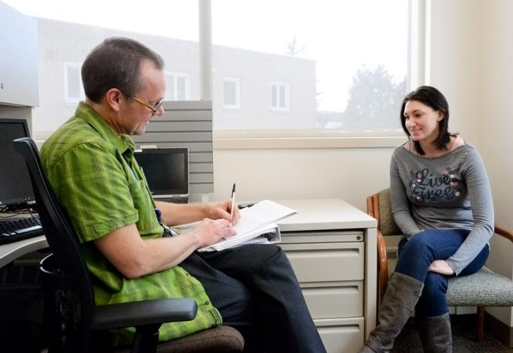 Male counselor taking notes while talking to female vet