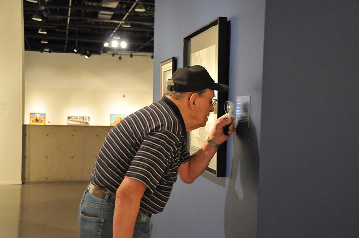 Image of a man using a magnifying glass to read a plaque at a museum.