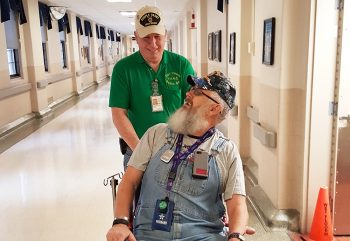 Image of a volunteer pushing a patient in a wheelchair.