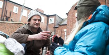 Homeless woman sitting on the street in the cold. A kind male offers her a hot drink from a flask.©iStock/SolStock