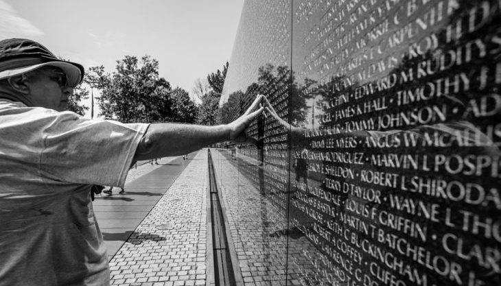 Image of a man touching the Vietnam memorial Wall