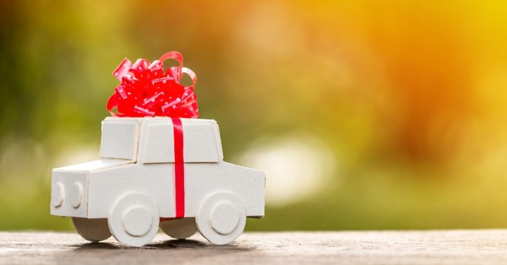 Image of wooden toy car with a bow tied around it.
