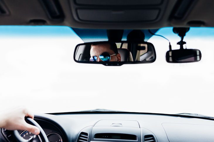 Point of view image peering through the windshield of a automobile.