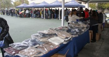 image of a long line of Veterans shopping for clothes set up under numerous tents