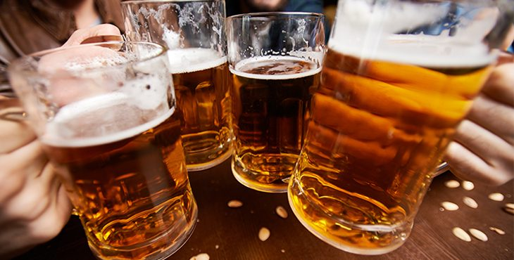 Image: Four people toasting with beer mugs