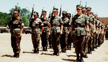 The Marine Corps' first all-woman drill platoon stands at attention in formation with M-16A1 rifles. The platoon was commanded by 1st Lt. Marie G. Juliano.