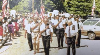 Image of people marching in a parade in the mid 70s.