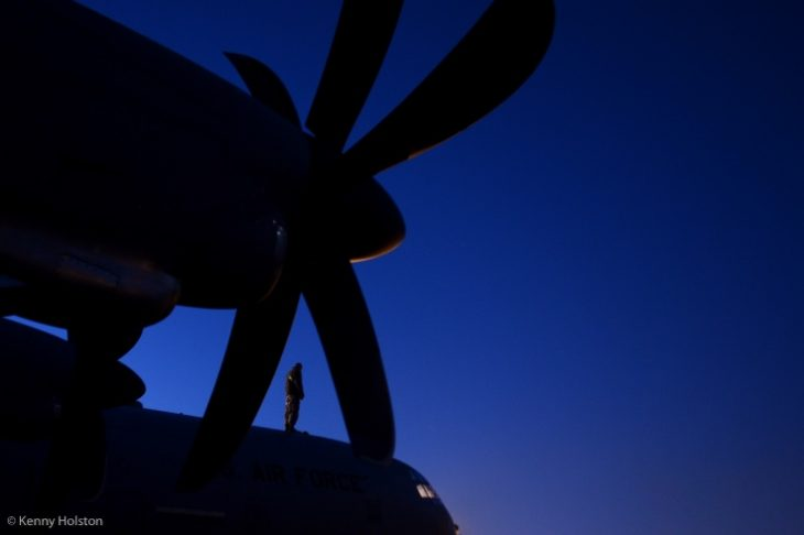 IMAGE: of a service member a top of a C130.
