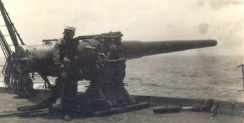 IMage of a sailor and a large gun on the USS Mongolia