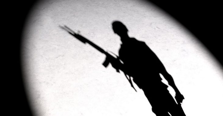 Image: a shaddow of a soldier projected onto a wall with a bright light.