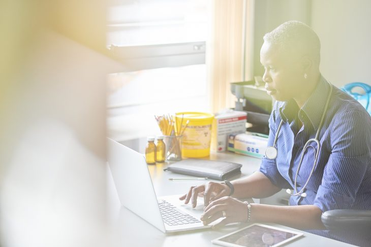A female doctor sits at her desk and checks something on her computer She is wearing a blue shirt with the sleeves rolled up and has her stethoscope around her neck. She is lit by bright window light .