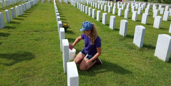 Image: A young girl on her kness cleaning a headstone at Jacksonville National Cemetery