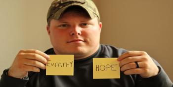 Image of a man holding two post-it notes with the words empathy and hope.