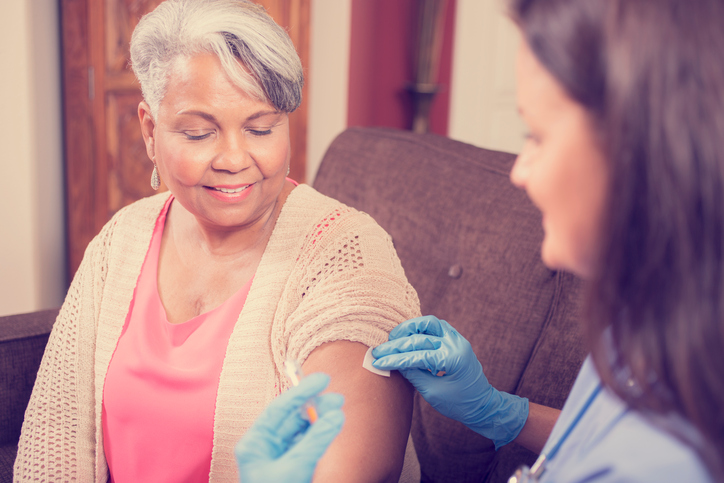 Caring, Latin descent home healthcare nurse gives vaccine or medicine injection to African descent senior adult patient at home, assisted living, or nursing home setting. She holds the syringe and wears protective gloves. The female patient happily receives the shot while sitting on her comfy sofa. Kitchen background.