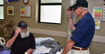 Image: A volunteer salutes a hospitalized Vetern siting on his bed.