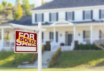 "Sold placard on house ""for sale"" sign in front of house"