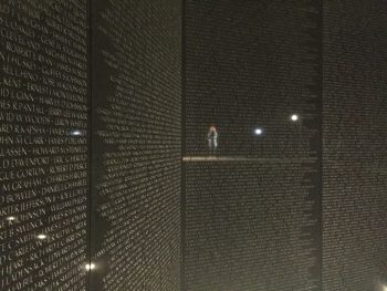 Reflection of woman reading names on the wall