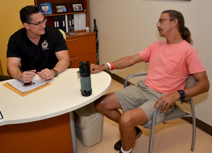 Tampa VA vocational rehabilitation specialist Todd Goldin talks with Army Veteran Patrick Stamm during the Veteran's recent reevaluation at the hospital. By coincidence, Goldin's mother, Judie Pink-Goldin, was one of Stamm's original occupational therapists after a four-story fall caused massive injuries and brought him to Haley in 1996 for recovery and rehabilitation.