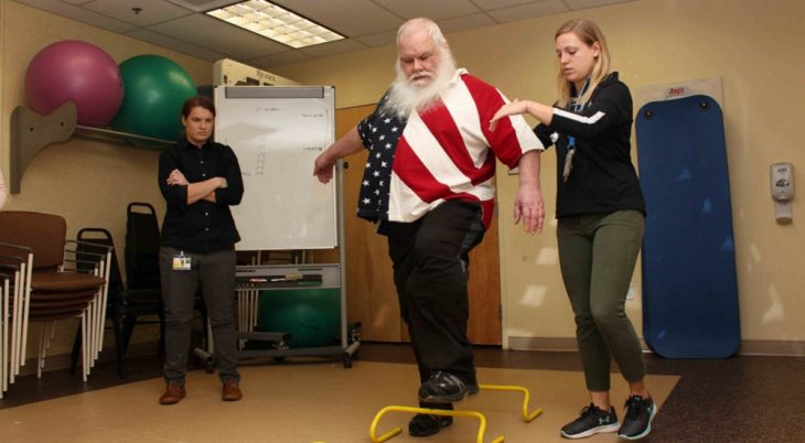 Army Veteran Gary Lucas navigates a hurdle exercise with the help of study coordinator Lydia Paden.