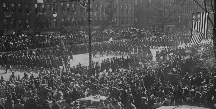 """Black and white photograph of the 369th """"Harlem Hellfighters"""" Regiment homecoming parade. Thousands of people line the streets as the soldiers march in formation."""