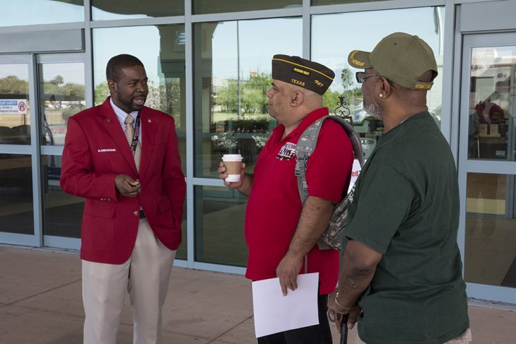 VA Red Coat Ambassador Fabian Cauldwell speaks with Army Veterans Roy Maggard and Fred Patton, who stopped by the VA Health Care Center at Harlingen, Texas on March 20, 2018.