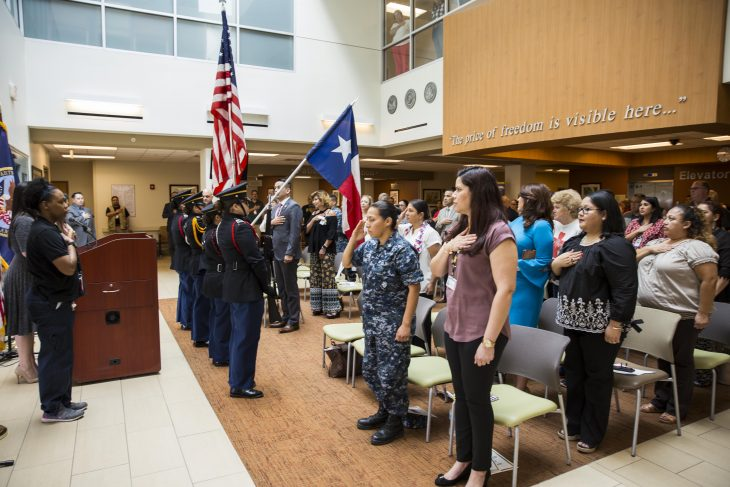 """Guests rise to their feet with render salutes and hands over their chest as the Harlingen High School All-Female Army Junior ROTC Color Guard present the colors, while the """"Star Spangled Banner"""" is sung by Mrs. Rebecca Arismendi, during the VA Texas Valley Coastal Bend Health Care System's ceremony in observance of national Women's History Month, which took place March 2, 2018, at the VA Health Care Center at Harlingen, Texas."""
